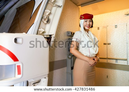 DUBAI, UAE - CIRCA MAY, 2016: Emirates crew member meet passengers on board of Boeing 777. Emirates is one of two flag carriers of the UAE along with Etihad Airways and is based in Dubai. - stock photo
