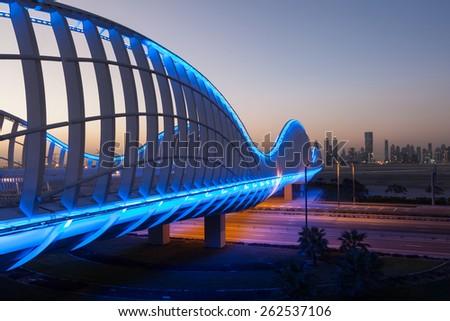DUBAI, UAE - DEC 13: Wave shaped Meydan Bridge in Dubai illuminated at night. December 13, 2014 in Dubai, United Arab Emirates - stock photo