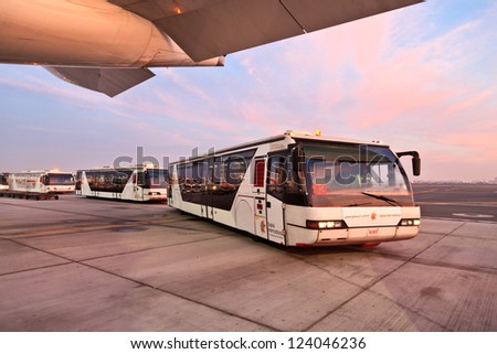 DUBAI, UAE - DECEMBER 26: Buses carrying passengers at Dubai Airport on December 26, 2012 in Dubai, UAE. Dubai airport is major aviation hub in the Middle East.