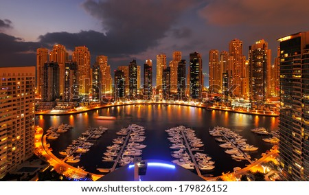 DUBAI, UAE - FEB 19: A view of Dubai Marina at Dusk showing numerous skyscrapers of JLT on Feb 19, 2014 in Dubai, UAE. Dubai Marina is an artificial 3 km canal carved along the Persian Gulf shoreline - stock photo