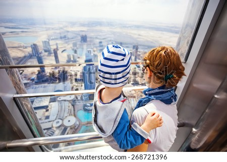 DUBAI, UAE - FEBRUARY 24: Young woman and her toddler son looking out of the window, while visiting At The Top - Observation Deck of Burj Khalifa. Picture taken on February 24, 2015. - stock photo