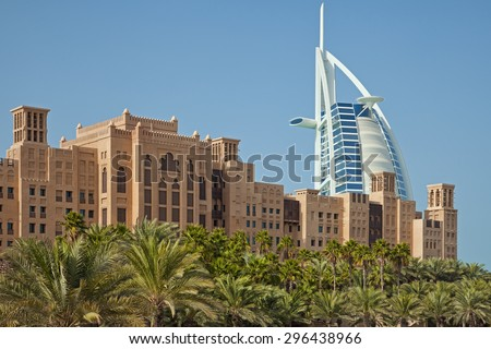 DUBAI, UAE - JANUARY 14, 2013: Arabic style buildings and rows of palm trees at Madinat Jumeirah in front of Burj Al Arab. Burj Al Arab is a luxury 7 star hotel, built on an artificial island. - stock photo