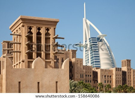 DUBAI, UAE - JANUARY 14: Arabic style buildings of Madinat Jumeirah in front of Burj Al Arab on January 14, 2013 in Dubai, UAE. Burj Al Arab is a luxury 7 star hotel, built on an artificial island. - stock photo