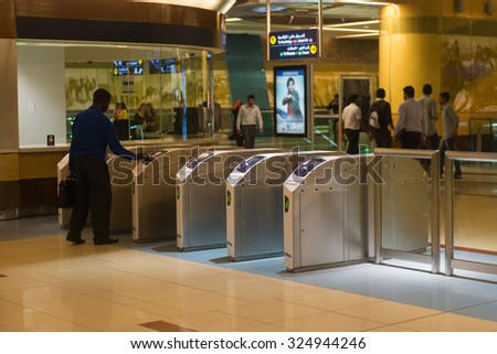DUBAI, UAE - 16 JULY 2014: Interior of a metro commuter train station with automated turnstyles in urban Dubai.