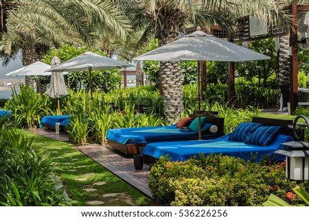 DUBAI, UAE - JUNE 26, 2016: Rixos The Palm Dubai - luxury multi-concept resort (230 rooms and suites) at end The Palm Jumeirah crescent. Beautiful area of resort are dotted comfortable sun loungers.