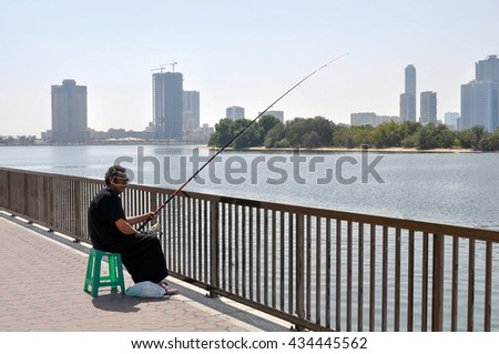 DUBAI,UAE - MARCH 09,2012 :a Man catches a fish on a bait on the waterfront in the state of Sharjah