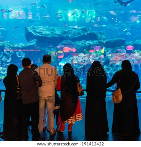 DUBAI, UAE - MARCH 28, 2014: People in front of the Oceanarium inside Dubai Mall. At over 12 million sq ft, it is the world's largest shopping mall. - stock photo
