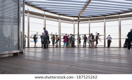 DUBAI, UAE - MARCH 29, 2014: People on Burj Khalifa observation terrace. Burj Khalifa is the tallest man-made structure in the world, at 829.8 m (2,722 ft).