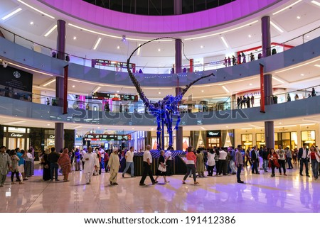 DUBAI, UAE - MARCH 28, 2014: People walking inside Dubai Mall. At over 12 million sq ft, it is the world's largest shopping mall.  - stock photo