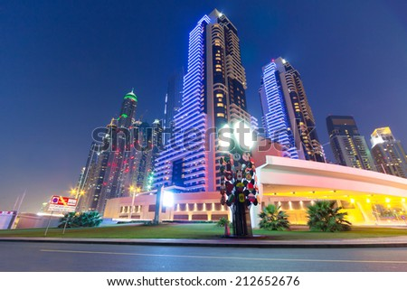 DUBAI, UAE - MARCH 30: Skyscrapers of Dubai Marina at night on March 30, 2014, UAE. Dubai Marina is a district in Dubai with artificial canal city who accommodates more than 120,000 people. - stock photo