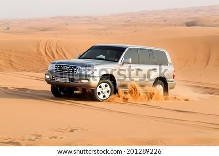 DUBAI, UAE - MAY 22: Driving a 4-wheel drive SUV on the desert. The Dubai desert trip in off-road car is major tourists attraction in Dubai on May 22, 2010 in Dubai, UAE - stock photo
