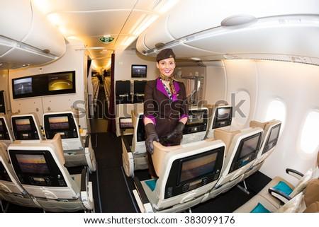Dubai, UAE - NOVEMBER 09, 2015: Etihad Airways flight attendant, cabin crew member. Etihad Airways economy class seats. Etihad stewardess. Etihad Airways Airbus A380 on November 09, 2015 in Dubai - stock photo