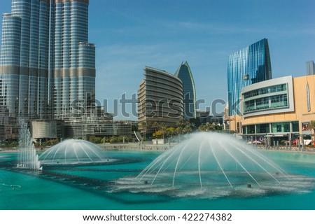 DUBAI, UAE - NOVEMBER 14: High rise buildings and fountains nov 14. 2012  in Dubai, UAE.  Burj Khalifa, the tallest building in the world - stock photo