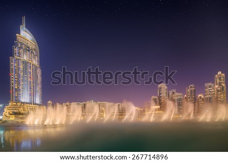 DUBAI, UAE - NOVEMBER 25, 2014: The Dancing Fountain of Dubai performs to the beat of the selected music at dusk near Burj Khalifa and  Dubai Mall in downtown of Dubai. Located on Sheikh Zayed Road.