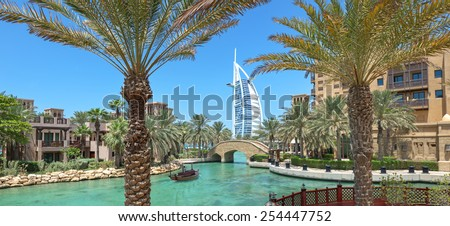 "DUBAI, UAE - SEPTEMBER 1, 2014: A panoramic view of the world's first seven stars luxury hotel Burj Al Arab ""Tower of the Arabs"", Madinat Jumeirah in Dubai  with palms tree  - stock photo"