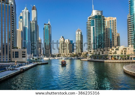 DUBAI, UAE - SEPTEMBER 8, 2015: Boat and modern skyscrapers in Dubai Marina. Marina - artificial canal city, carved along a 3 km stretch of Persian Gulf shoreline.