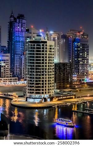 DUBAI, UAE - SEPTEMBER 29, 2012: Night view at modern skyscrapers in Dubai Marina. Marina - artificial canal city, carved along a 3 km stretch of Persian Gulf shoreline. Dubai, United Arab Emirates. - stock photo