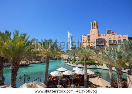DUBAI, UNITED ARAB EMIRATES - APRIL 11, 2016: View of Burj Al Arab hotel from the Souk Madinat Jumerirah with palm trees . April 11, 2016 Dubai, United Arab Emirates - stock photo