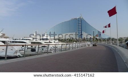 Dubai, United Arab Emirates - February 12, 2016 : Jumeirah Beach hotel with the pure white sand beach and luxury cruises, surrounded by green palm trees. Voted the Best Hotel in the Middle East - stock photo