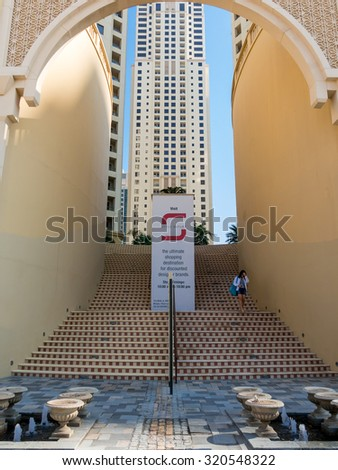 DUBAI, UNITED ARAB EMIRATES - JAN 25, 2014: Woman walking down stairs of shopping centre The Walk in the Marina district of Dubai, United Arab Emirates - stock photo