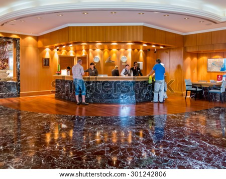 DUBAI, UNITED ARAB EMIRATES (UAE) - JAN 25, 2014: Receptionists and guests at reception desk in hotel beach resort in Dubai, United Arab Emirates - stock photo