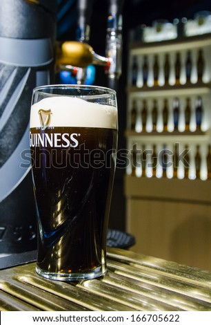 DUBLIN, IRELAND - NOV 11, 2013: Pint of beer served at Guinness Brewery on November 11, 2013 in Dublin. Brewery where 2.5 million pints of stout are brewed daily was founded by Arthur Guinness in 1759 - stock photo