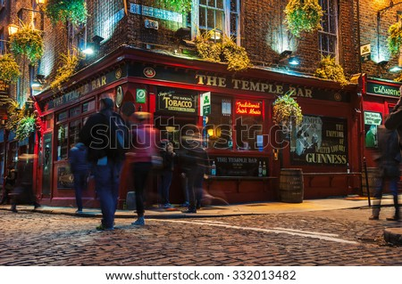 DUBLIN, IRELAND - NOVEMBER 11, 2014: Nightlife at popular historical part of the city - Temple Bar quarter. The area is the location of many bars, pubs and restaurants. People walking inside a pub - stock photo