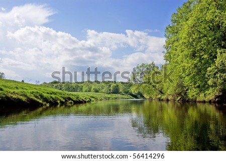 Dubna river (Russia) in surroundings greenery in a hot summer day