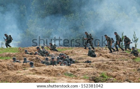 DUBOSEKOVO, RUSSIA - JULY 13: military history club members in WWII German uniform overrun the trenches  during Field of Battle military history festival on July 13, 2013 in Dubosekovo, Russia  - stock photo