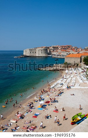 DUBROVNIK, CROATIA - JULY 21, 2013: Dubrownik old city castle and walls with tourists at the Banje beach