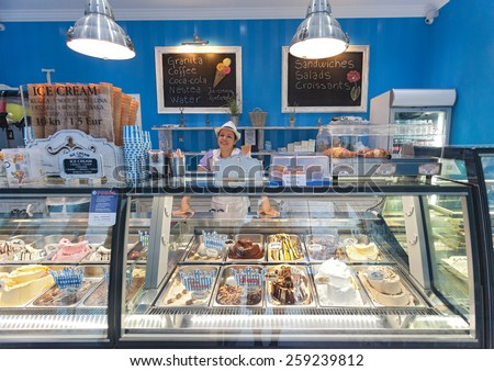 DUBROVNIK, CROATIA - MAY 26, 2014: Smiling young waitress at Gossip ice cream shop on main street Stradun. It is one of the best ice cream place in town popular among tourists. - stock photo