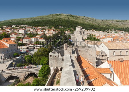 DUBROVNIK, CROATIA - MAY 26, 2014: View on Old city rooftops walls and and Srdj hill in the background. - stock photo