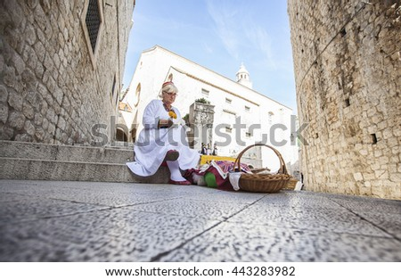 DUBROVNIK, CROATIA-OCT. 25:A woman wear traditional clothing to sell handicrafts at the unesco world heritage of old town Dubrovnik on Oct. 25, 2015, Croatia.