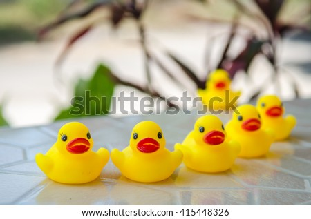 Duck dolls, toys for children, on a table made of wood and background bogey tree. (Select focus)