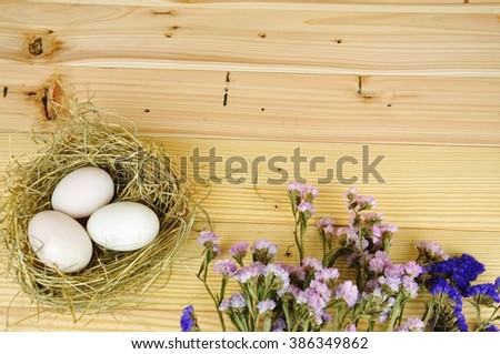 Duck eggs in a nest decorate with pink and purple flowers on the wooden table.Easter festival. - stock photo