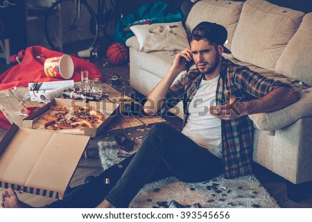 Dude where are my shoes? Handsome young man talking on mobile phone and gesturing while sitting on the floor in messy room after party - stock photo