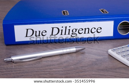 Due Diligence binder blue color on desk in the office