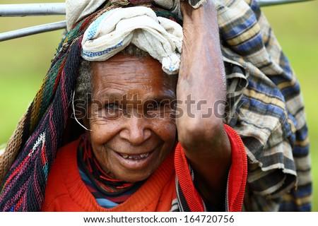 DUGUM DANI VILLAGE, BALIEM VALLEY, IRIAN JAYA, NEW GUINEA, INDONESIA -Â?Â? July 18, 2013:  On July 18, 2013 in Dugum Dani Village, New Guinea, Indonesia. Dani woman in a traditional dress, cap on a head. - stock photo