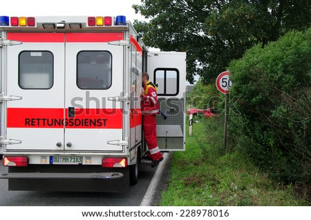 DUISBURG, GERMANY - 26 JULY 2011 The ambulance car on an incident place, the hospital attendant renders a psychological assistance - stock photo