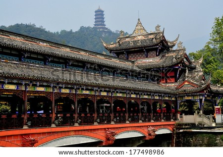 Dujiangyan, China - October 9, 2013:  The Ming Dynasty Nan Qiao covered bridge over the Min River with distant hilltop pagoda - stock photo