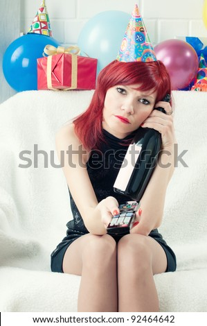 Dull birthday: bored party woman watching TV at home - stock photo