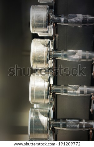 Dumb bells lined up in a fitness studio  - stock photo