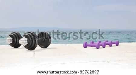 Dumb bells on the beach - stock photo