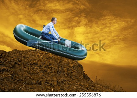 Dumb funny Business man stop on pick mountain boat businessman rock look bright future symbol crisis stagnation losses braking difficulties environmental disaster water scarcity drought on sunset sky - stock photo
