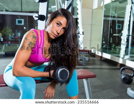 dumbbell concentrated biceps curl girl woman workout at gym exercise - stock photo