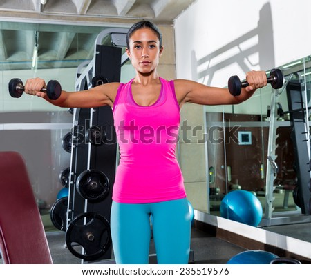 dumbbell front shoulder flies fly woman workout exercise at gym - stock photo