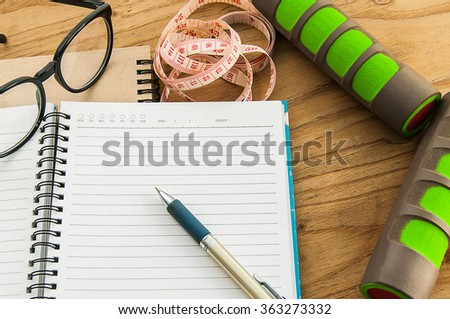 Dumbbell,measuring tape, glasses with diary book on wood background, exercise program fitness concept, Planning control diet concept. - stock photo