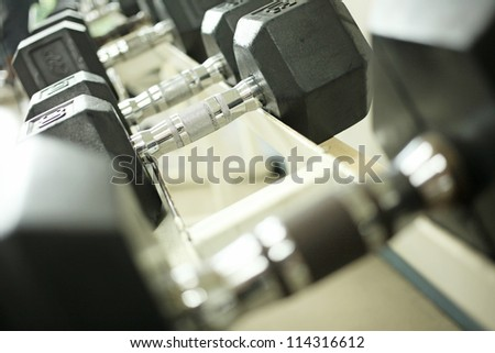 dumbbell rack, black four dimension dumbbells on rack - stock photo