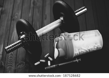 Dumbbell, shaker with tablets and syringe over wooden background - stock photo