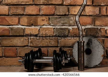Dumbbells and barbell against brick - stock photo